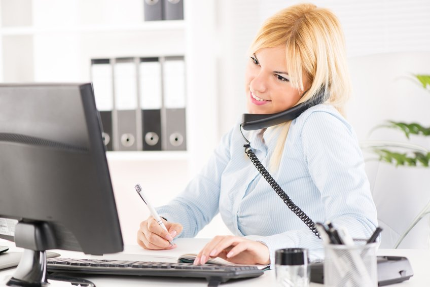 A woman sitting at a desk on the phone typing